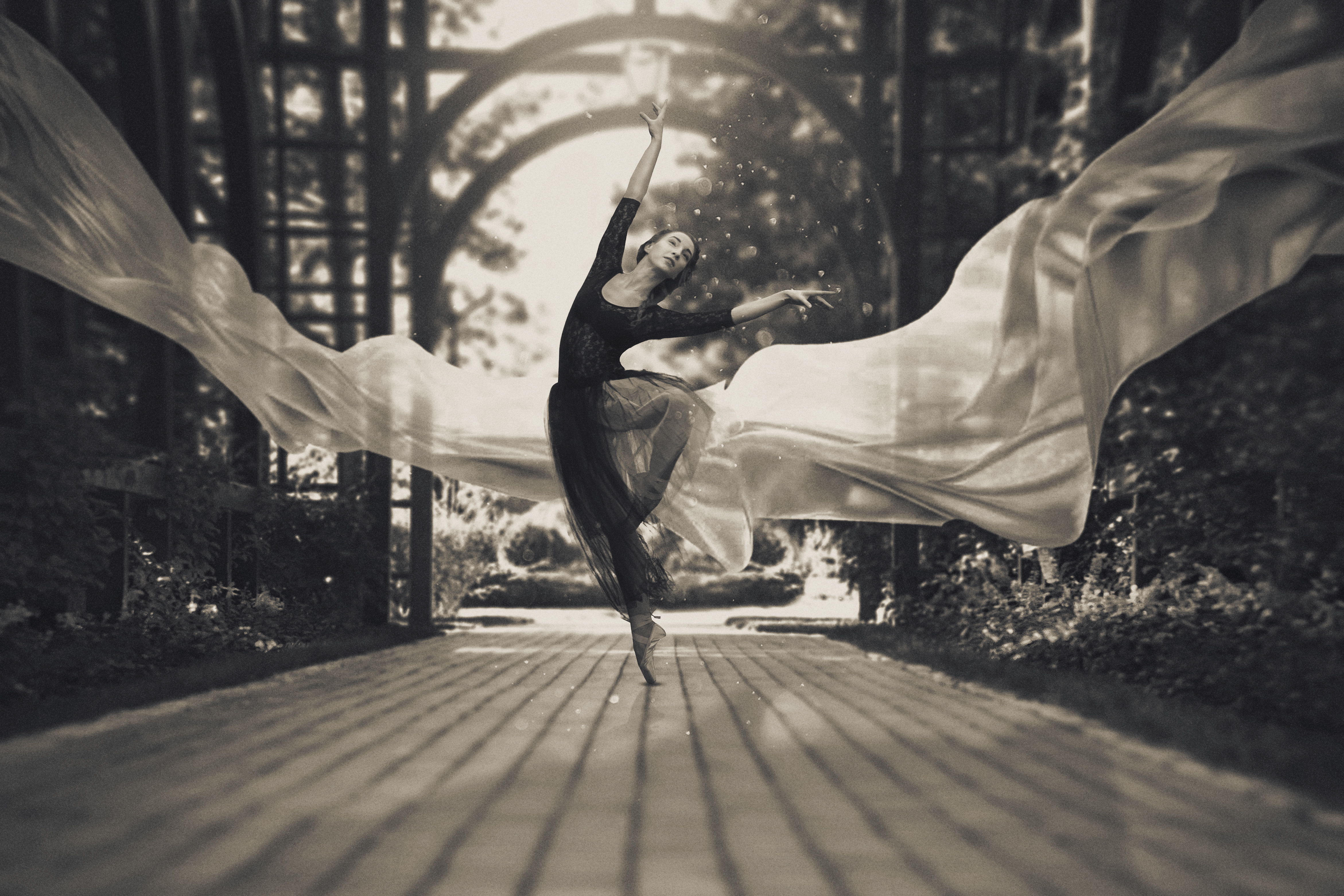 Ballerina out of doors, young modern ballet dancer posing. Black and white photography. The fabric in the air